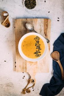 Eine schüssel mit kürbissuppe auf einem hölzernen brett und einem blauen küchenstoff beiseite