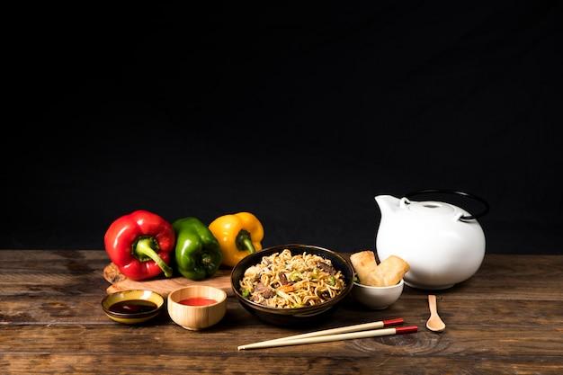 Eine schüssel mit leckerem rindfleisch-teriyaki mit udon-nudeln; soja soße; paprika- und frühlingsrolle mit essstäbchen und löffel auf holztisch