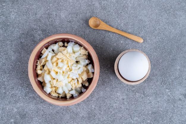 Eine schüssel mit leckerem salat und gekochtem ei. hochwertiges foto