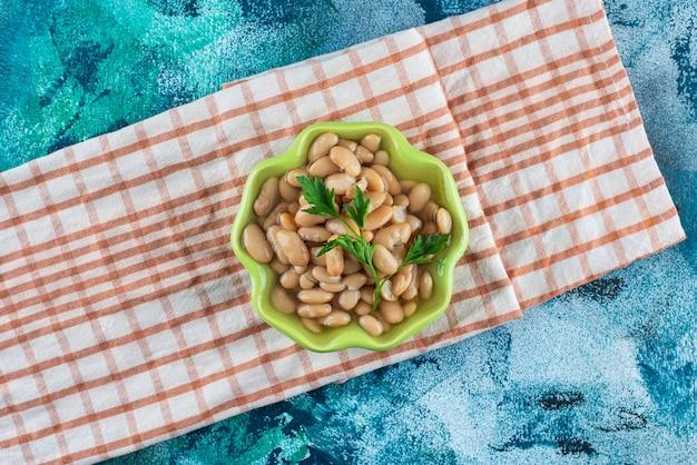 Eine schüssel mit leckeren gebackenen bohnen auf einem geschirrtuch auf dem blauen tisch.