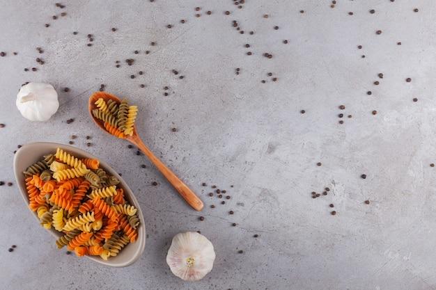 Eine schüssel mit mehrfarbigen rohen spiralnudeln mit knoblauch- und pfefferkörnern.