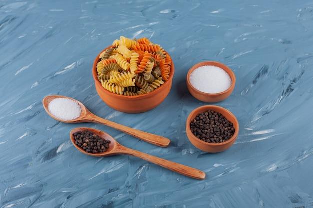 Eine schüssel mit mehrfarbigen rohen spiralnudeln mit salz- und pfefferkörnern.