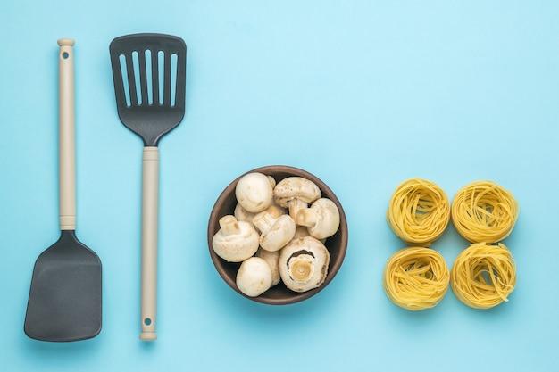 Eine schüssel mit pilzen, küchenspateln und vier knäuel nudeln auf blauem grund. zutaten für die herstellung von nudeln.