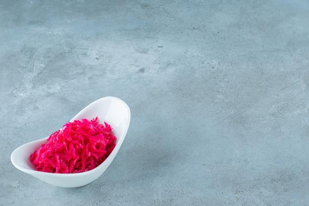 Eine schüssel mit rot fermentiertem sauerkraut, auf dem blauen tisch.