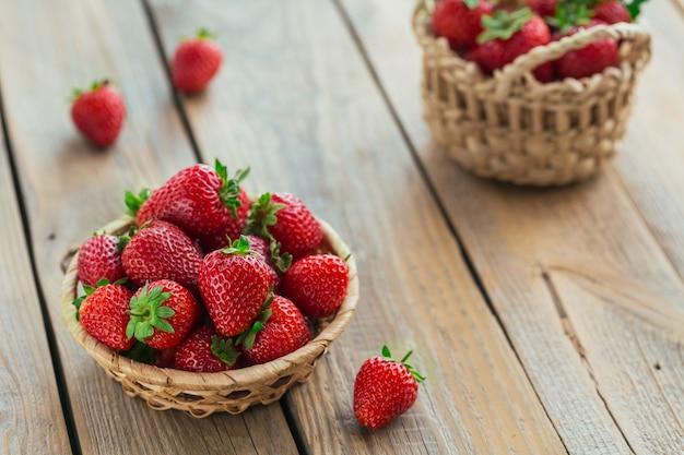 Eine schüssel mit roten saftigen erdbeeren auf rustikalem holztisch. gesundes und diät-snack-food-konzept.