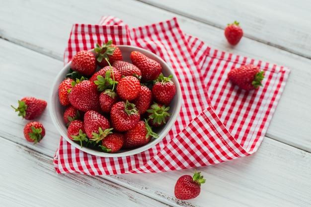 Eine schüssel mit roten saftigen erdbeeren auf weißem holztisch