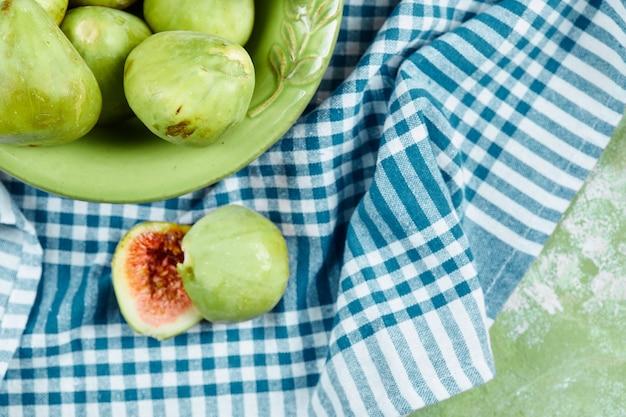 Eine schüssel mit saftigen grünen feigen und feigenscheiben auf blauer tischdecke.