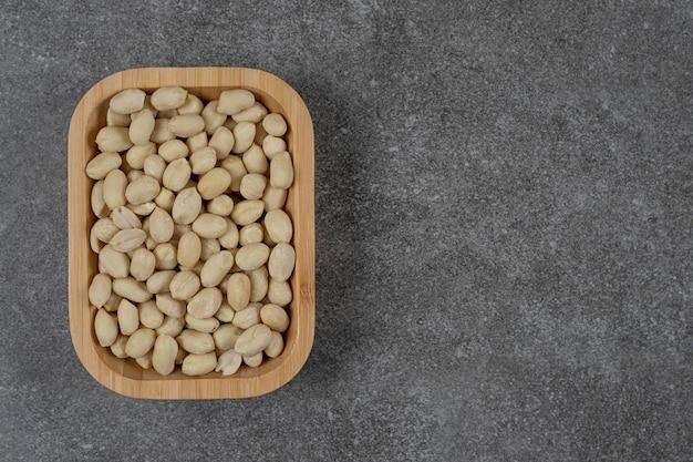 Eine schüssel mit schalenlosen erdnüssen auf der marmoroberfläche