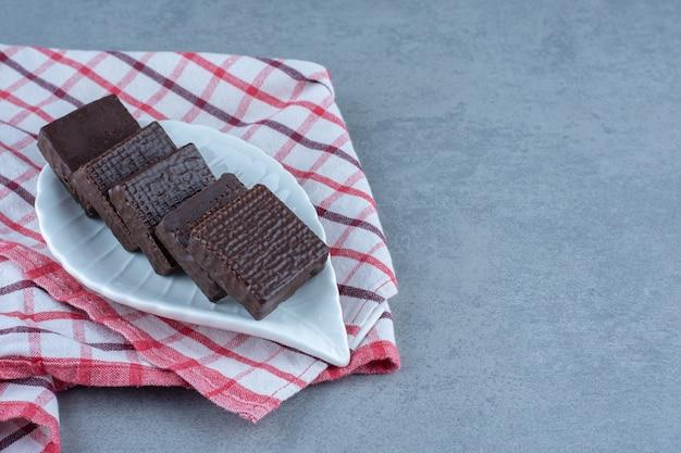 Eine schüssel mit schokolade überzogen auf einem knusprigen waffelriegel auf dem handtuch, auf dem marmortisch.