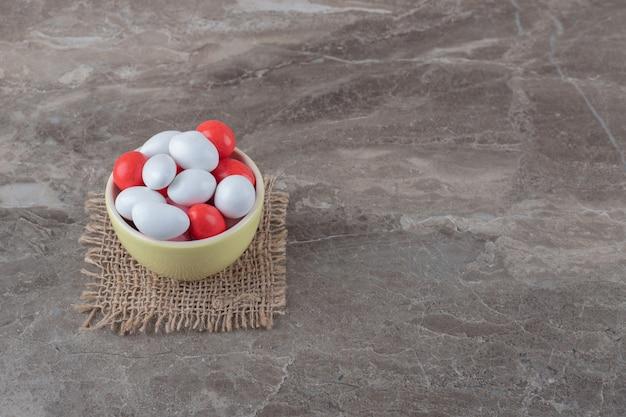 Eine schüssel mit süßigkeiten auf dem untersetzer, auf der marmoroberfläche