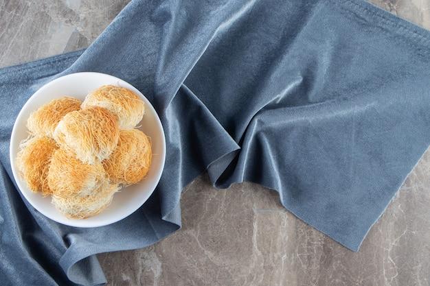 Eine schüssel mit türkischem dessert kadayif auf stoffstücken auf blau.