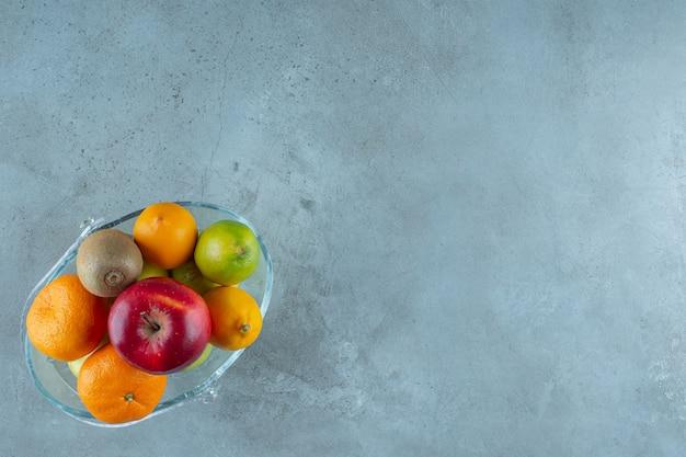 Eine schüssel mit verschiedenen früchten, auf dem marmorhintergrund. foto in hoher qualität
