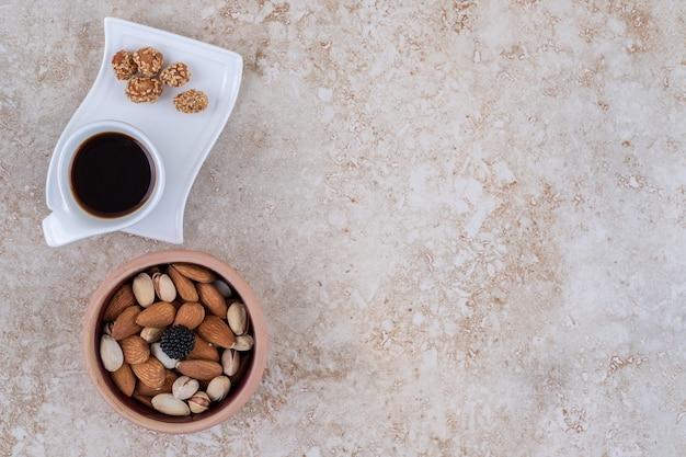 Eine schüssel mit verschiedenen nüssen und eine tasse kaffee
