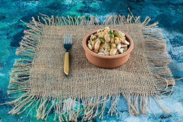 Eine schüssel mit weißen bohnen neben der gabel auf einer textur, auf dem blauen tisch.