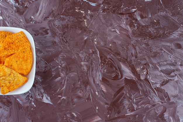 Eine schüssel mit würzigen würzigen chips auf dem marmortisch.