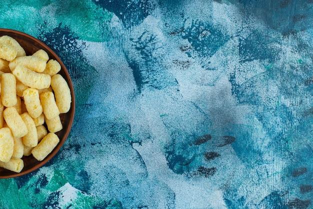 Eine schüssel mit zuckermaissticks auf dem blauen tisch.