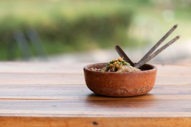 Eine schüssel nudel mit schweinefleisch und schweinefleischbällen mit suppe auf holz