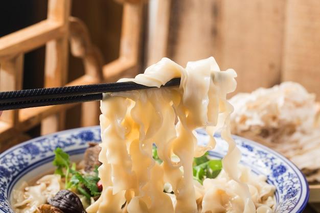 Eine schüssel nudeln mit geschmortem rindfleisch