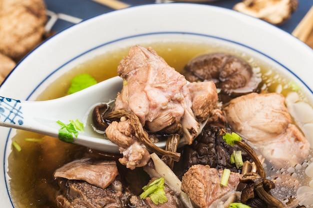 Eine schüssel pilz-lao-entensuppe auf einem schneidebrett