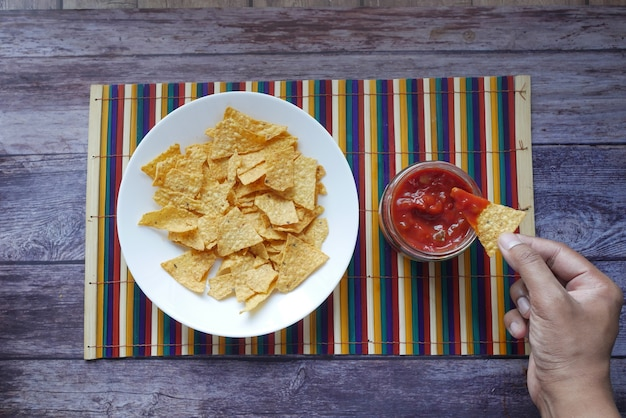 Eine schüssel pommes und salsa auf dem tisch