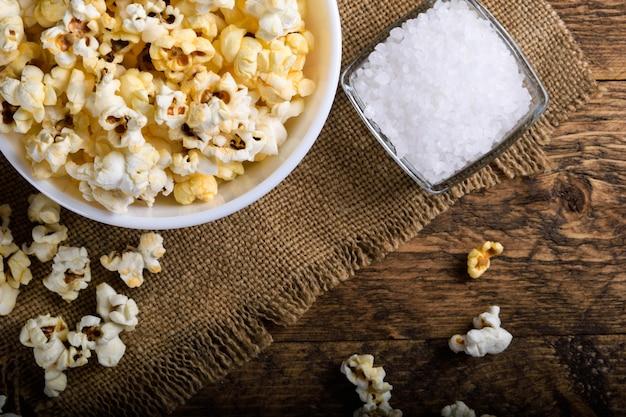 Eine schüssel popcorn auf einem holztisch