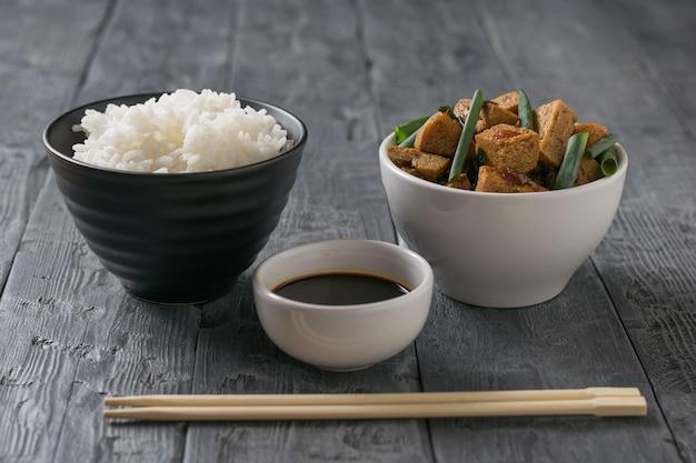 Eine schüssel reis, eine schüssel tofu und eine schüssel sojasauce