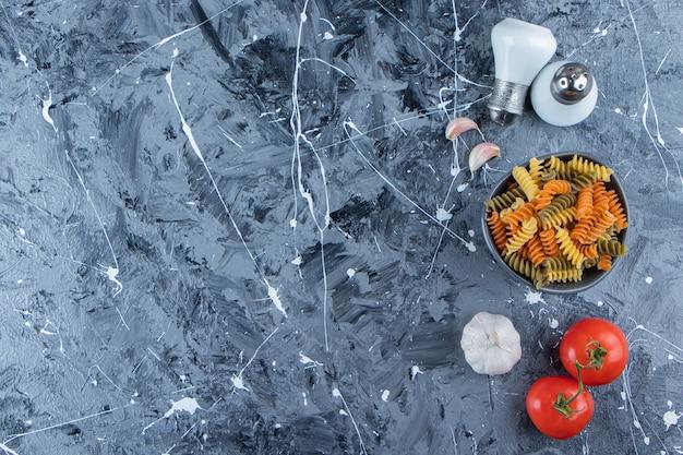Eine schüssel rohe nudeln mit frischem gemüse und gewürzen auf einem marmorhintergrund.