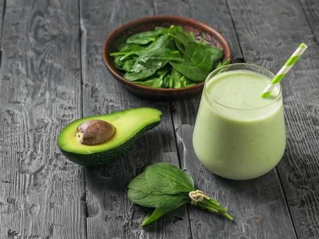 Eine schüssel spinatblätter, eine halbe avocado und ein glas smoothies auf einem schwarzen holztisch. fitnessprodukt. diätetische sporternährung.