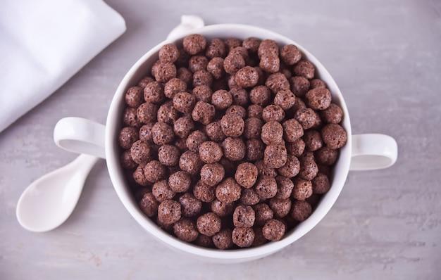 Eine schüssel trockenes schokoladenballgetreide auf der grauen tabelle zum gesundheitsfrühstück
