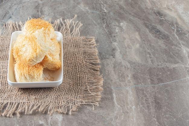 Eine schüssel türkisches dessert kadayif auf einer textur auf blau.