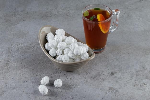 Eine schüssel voll süßer weißer bonbons mit einer tasse heißem tee auf einem steintisch.