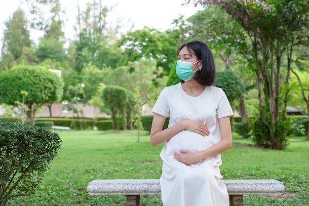 Eine schwangere asiatin in freizeitkleidung sitzt und trägt eine gesichtsmaske im park.