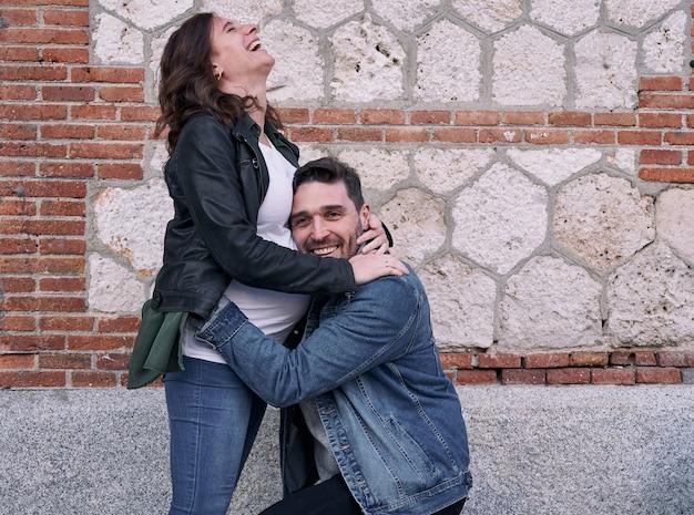 Eine schwangere frau, die vor einem backsteingebäude steht. mann umarmt ihren bauch. glückliches paar.