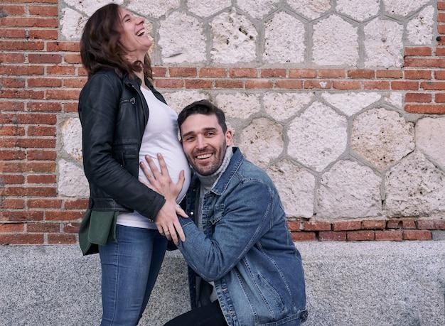 Eine schwangere frau, die vor einem backsteingebäude steht. mann umarmt ihren bauch. paar.