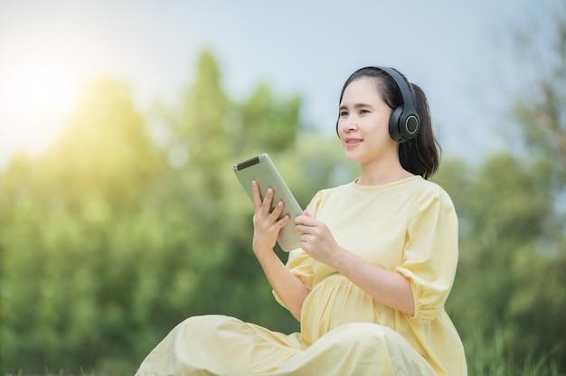 Eine schwangere frau entspannt sich im park und hört musik auf einem tablet, mama hört lieder für das ungeborene kind, schwangere bei der geburt, mutter und kind