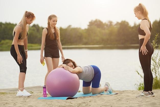 Eine schwangere frau entspannt sich mit einem gymnastikball in begleitung eines trainers und freunden am seeufer