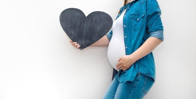 Eine schwangere frau hält eine leere tablettenschablone für ihren text.