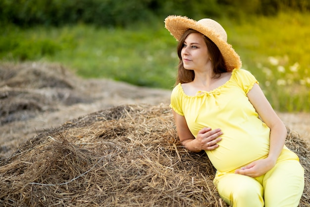 Eine schwangere frau in dunkler kleidung und einem hut sitzt im sommer auf einem feld auf stroh, ein spaziergang eines schwangeren mädchens in der natur