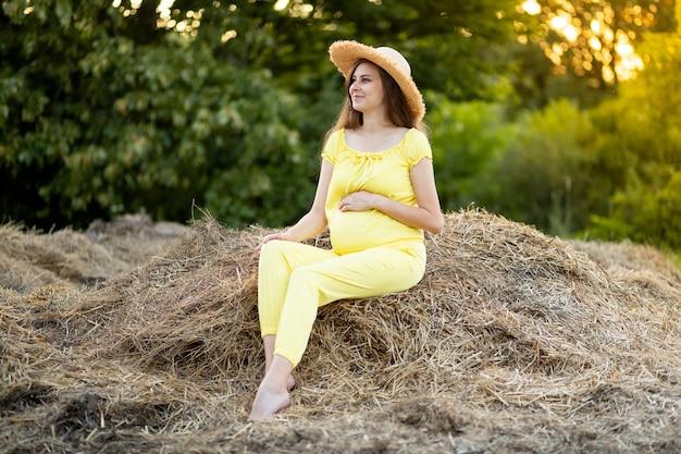 Eine schwangere frau in dunkler kleidung und einem hut sitzt im sommer auf einem feld auf stroh