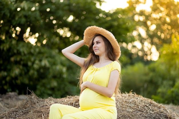 Eine schwangere frau in dunkler kleidung und einem hut sitzt im sommer auf einem strohfeld, ein spaziergang eines schwangeren mädchens in der natur