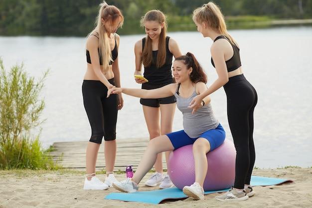 Eine schwangere frau macht mit einem trainer und freunden am seeufer fitness mit einem ball