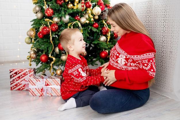 Eine schwangere frau mit einem baby in einem roten pullover unter dem weihnachtsbaum zu hause, die sich umarmt, sich gegenseitig gratuliert und das neue jahr und weihnachten genießt
