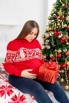 Eine schwangere frau mit einem geschenk im roten pullover unter dem weihnachtsbaum zu hause streichelt ihren dicken bauch und träumt von einem baby und genießt das neue jahr und weihnachten