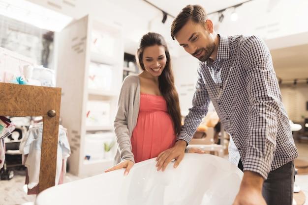 Eine schwangere frau mit einem mann wählen eine babywanne in einem geschäft.