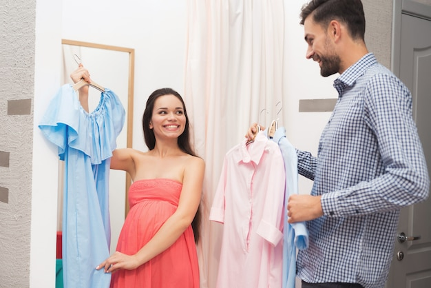 Eine schwangere frau mit einem mann wählt kleider im laden.