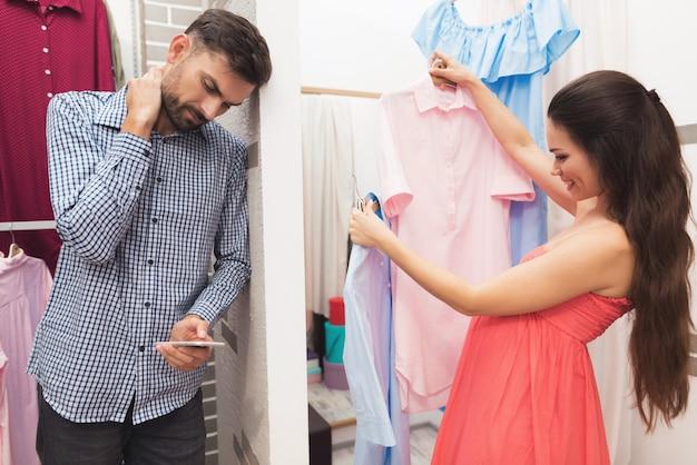 Eine schwangere frau mit einem mann wählt kleidung im laden.