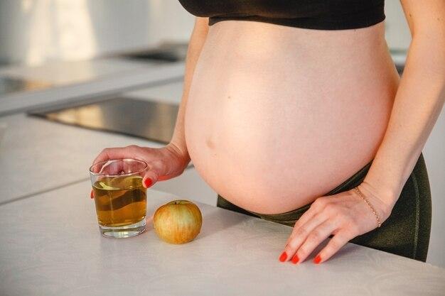 Eine schwangere frau mit nacktem bauch steht mit apfelsaft in den händen neben dem tisch. in der nähe ist der apfel
