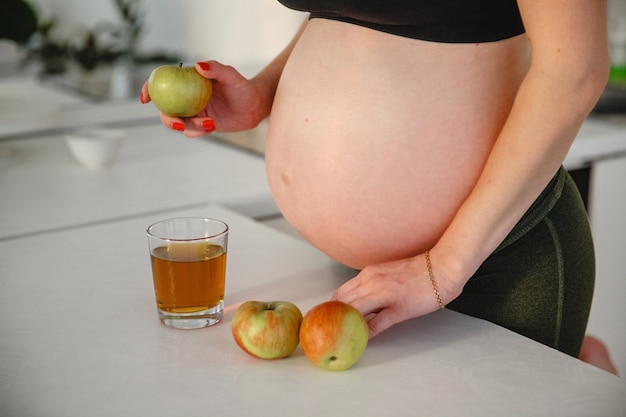 Eine schwangere frau mit nacktem bauch steht mit apple in den händen neben dem tisch. in der nähe ist das glas apfelsaft