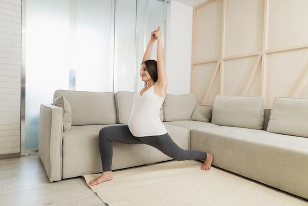 Eine schwangere frau sitzt zu hause auf einem hellen boden