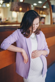 Eine schwangere frau streichelt ihren bauch. ein mädchen, das auf ein kind wartet, geht in ein einkaufszentrum. das konzept eines gesunden lebensstils, ivf, mode für schwangere, kinder